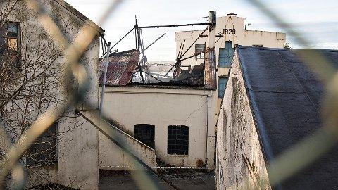 Den historiske fabrikkbygningen ble totalskadd i brann. Nå ønsker eierne å rive, men får ikke svar fra Time kommune før tidligst 25. oktober.