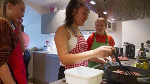 Randi Thrana steiker kjøtkaker. Oda Strømland (tv.) og Kaisa Rugland ser på.