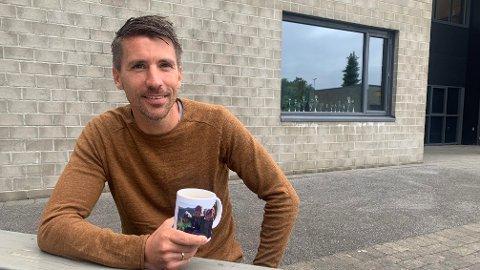 Vegar viser stolt frem koppen han har med bilde av barna.