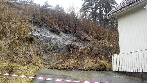 VED KYSTLEDHYTTA: Rasmassene har havnet tett inn mot grunnmuren til Kystledhytta ved Sandsletta. Helt øverst kan en stor sprekk i jordmassene såvidt skimtes.           FOTO: LARS IVAR HORDNES