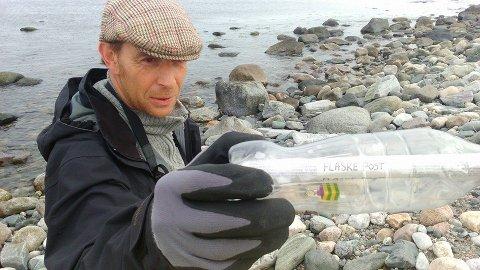 FRIERI: Roger Ehnebom står med flaskeposten han fant på Jomfruland under et oppdryningsarbeid, onsdag ettermiddag. Foto: Per-Erik Schulze/Naturvernforbundet.