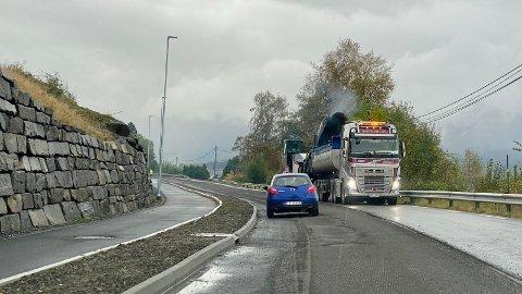 Det er asfaltarbeid i Neslia og manuell dirigering for tida. På bildet er det høvling av gamal asfalt som føregår.