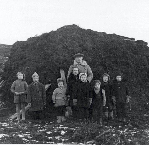 Lærer Ragnvald Mathiesen og elever foran gamme i Gamvik.
