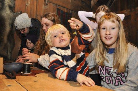 Isabell t.h. har akkurat hjulpet søskenbarnet Arnt-Aksel med å lage en skinnpung, som hun har lært å lage av Monika Hågensen t.v. Foto: Lise Fagerbakk
