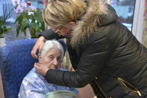 Forvirret: Jørgine Fredriksen får hjelp av datteren Solfrid Selsøvold til å sette i høreapparatet. Jørgine bruker ikke høreapparatet for å slippe støy og bråk fra ombyggingen til legevakt på Gravdal sykehjem.Begge foto: Karin P. Skarby