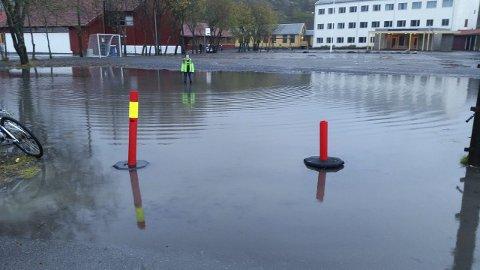 BASSENG:  Store deler av uteområdet ved Ballstad skoler er tidvis oversvømt av vann. Her har en elev tatt plass midt i innsjøen. Foto: Privat