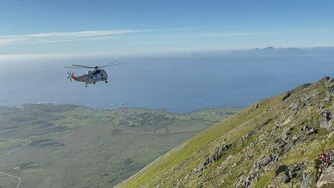 Er Sea King-helikopter har fraktet ned to utmattede personer fra fjellet Matmora ved Laukvik. Personene var deltakere på løpsarrangementet Lofoten Skyrace. Bildet er tatt av Lofotpostens redaktør, Jan Eivind Fredly, som selv er deltaker i løpet og derfor befant seg i området.