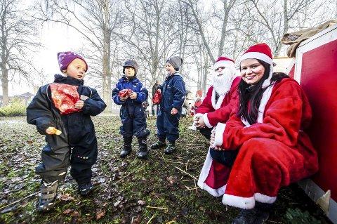 Nissen: Mathilde (til v), Noah Gellein og Levi Røyneberg var blant dem som fikk juleposer av nissen, på åpen julegård på Tomb lørdag. (foto: Johnny Leo Johansen)
