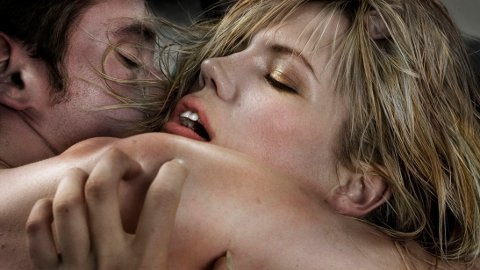 Naked young couple embracing, eyes closed, close-up
