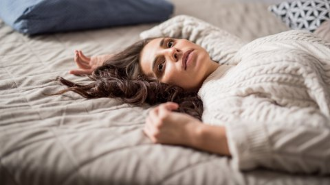Beautiful young woman laying in bedroom at home and contemplating.