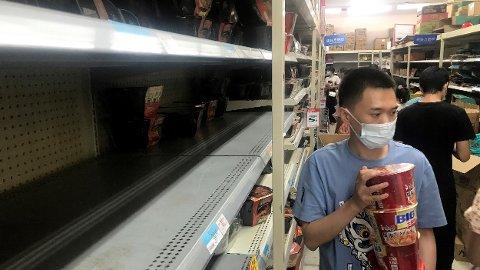 Hyllene er tomme etter at innbyggere i Wuhan har hamstret inn nødvendige matvarer på et supermarked etter at myndighetene varslet lockdown i en rekke boligområder.
