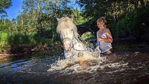 NØT VARMEN: Vilde Elvestad fra Steinkjer har under hetebølgen brukt mye tid sammen med sin hest Prakkari på Solheim i Ogndal. Det varme været har bidratt til at det har blitt bading både for firbeint og tobeint.