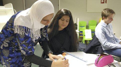 MATTEHJELP: Ashba Butt får hjelp av Hanan Abdelrahman til å lære den grunnleggende matematikken godt. I bakgrunnen: Emil Hengy. Foto: Trine Dahl-Johansen