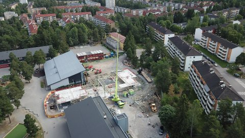 FRA LUFTA: På dette dronebildet ser man tydelig hvordan nybygget reiser seg og blir liggende på skoleområdet. FOTO: A Bygg Entreprenør