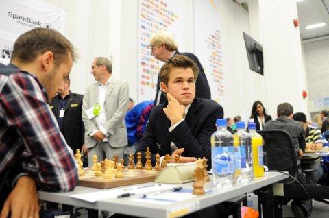 Magnus Carlsen i aksjon under sjakk-OL i Tromsø, med folk rundt seg på alle kanter. Carlsen mener forholdene under OL var medvirkende for hans egne skuffende prestasjoner.