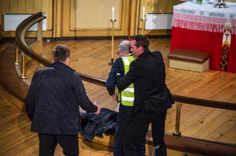 TATT MED: Abortmotstander Per Kørner blir tatt med bort fra alteret. Foto: Stian Joachim Olsen.