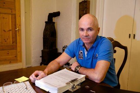 Helge Horne med ringpermen som inneholder en del av dokumentasjonen knyttet til skaden han pådro seg i 2010.