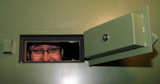 INNENFRA: Politimester Ole B. Sæverud titter gjennom kikkhullet på ei glattcelle i arresten.
