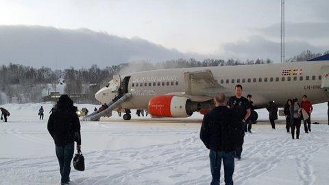 EVAKUERT: Her forlater passasjerene flyet på Tromsø lufthavn. Røyken kan synes i fronten av flyet.