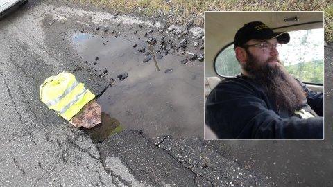 HULL: Bjørn-Steinar Hanssen fortviler over den dårlige fylkesveien. Her satte han en vedsekk i veien for å varsle andre bilister om et stort hull.