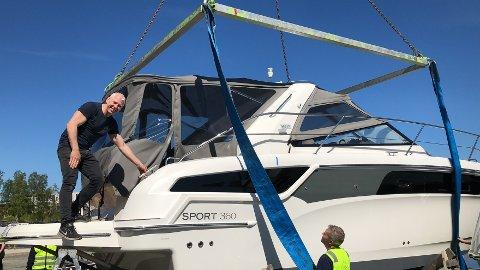 HEISES PÅ PLASS: Roger Stende rekker å legge på plass putene i båten, rett før cabincruiseren heises på vannet.