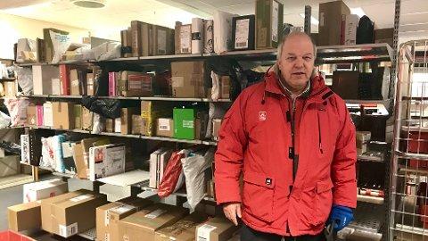 FYLLES OPP: Pakkehyllene inne på postkontoret i Hamar er sprengt. Roar Bjørke anbefaler folk å hente pakkene sine. (Foto: Jo Espen Brenden)