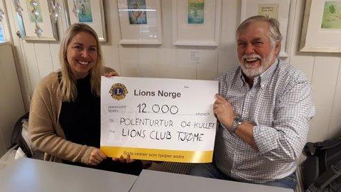 Yngve Lindgaard-Berntsen i Lions overrekker en sjekk på 12.000 kroner til foreldregruppas representant, Linda Larsen Vassbotn.