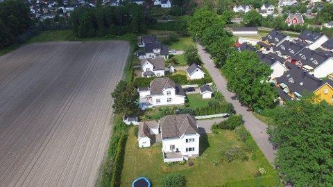 Klager hevder at oppkjøpte eiendommer i Eikeveien forfaller mens planene om fastlandsforbindelsen er i det uvisse. Nåværende veiplaner vil berøre rekken med hus som ligger ved jordet på bildet.