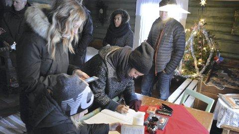 På besøk: Ingeborg S. Raustøl signerer gjesteboka i Prøysenstua, mens resten av staben står i kø.