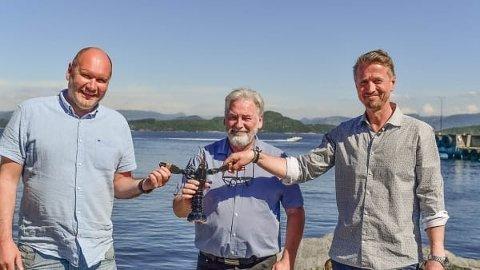 HUMMER: Fra venstre: Tor Kristian Gyland (Green Mountain), Alf Reime og Asbjørn Drengstig (Norwegian Lobster Farm) med en hummer.
