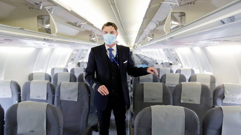 VURDERER MIDTSETEKRAVET: Nå skal kravet om at midtsetet i flyene må være blokkert kanskje fjernes. Her er SAS-crew Jon-Anders med munnbind, som er påbudt på SAS sine flyvninger under koronakrisen. Foto: Vidar Ruud (NTB scanpix)