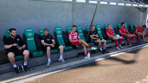 GOD BREDDE: Strømmen-trener Ole Martin Nesselquist (t.v.), assistent Steffen Andersen og de andre holder god avstand på Strømmen-benken. Treneren mener at han disponerer en bred spillerstall denne sesongen.