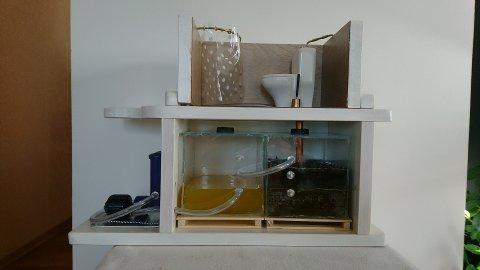 MODELLEN: Modell som viser et komplett anlegg med toalett/bad på toppen. Under ser man en tank med bark (mørk) der omdanningen skjer. Væsken renner over i tank nr 2 (gulaktig) og blir senere filtrert gjennom et omvendt osmosefilter lengst til venstre.