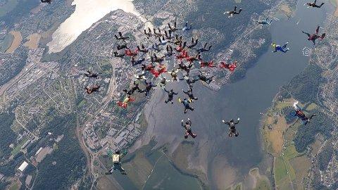 HØYT OG FORT: 52 fallskjermhoppere på full fart nedover mot Vestfolds jorder. Målet var å sette ny norsk rekord. Under hopperne ser vi Tønsberg.