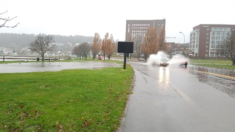 IKKE SLIK: Her blir en taxi overøst med store mengder vann søndag formiddag.