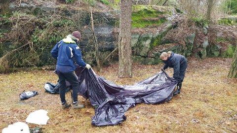 Caroline Bjørnstad og Sindre Bergsvåg pakker sammen en telt som har kollapset i regnet.