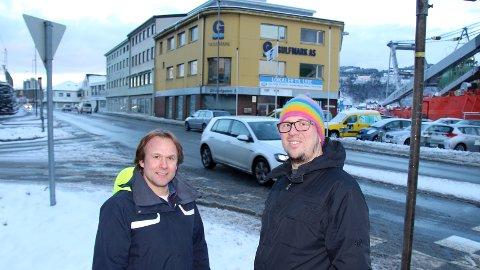 ØNSKER BEVARING: Erlend Kristensen (MdG) og Kjell Haavard Thrane Høie (V) ser helst at byggene i bakgrunnen rustes opp og blir stående. Flertallet i bystyret går inn for å fjerne vernestatusen.