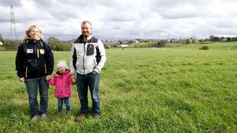BY MØTER LAND: Anne Margrethe Kyllingstad, datter Marita og Martin Folkvord har 57 årskyr og melkekvote på 500.000 liter i året på Folkvord. I bakgrunnen ser vi byen reise seg.