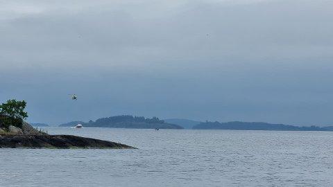 Båten flyter i fjorden. Redningsskøyte og helikopter er her på vei mot båten, som du ser i midten av bildet.