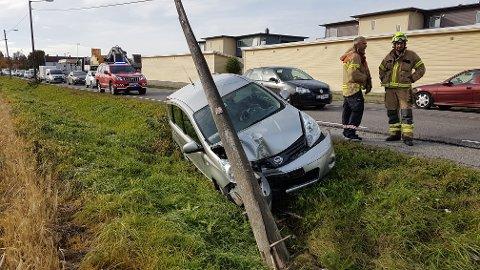En bil har kjørt av veien og kollidert med en stolpe.