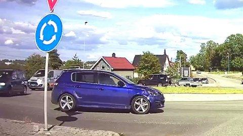 Den blå bilen i forgrunn av bildet har kollidert med den sorte bilen på andre siden av rundekjøringen.