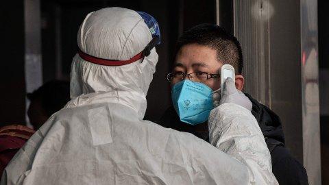 Kinesisk helsepersonell sjekker for symptomer på coronaviruset.