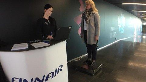 Én av Finnairs passasjerer lar seg frivillig veie ved innsjekkingen på flyplassen i Helsinki.