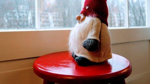 En rødmalt krakk ved vinduet skaper julestemning.