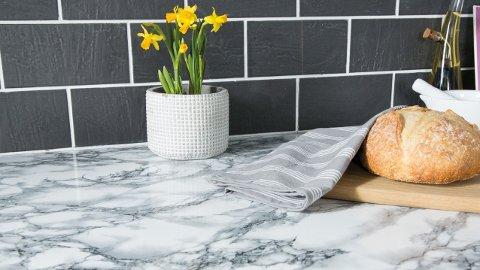Her er det brukt selvklebende designfolie med marmorlook på kjøkkenbenken.