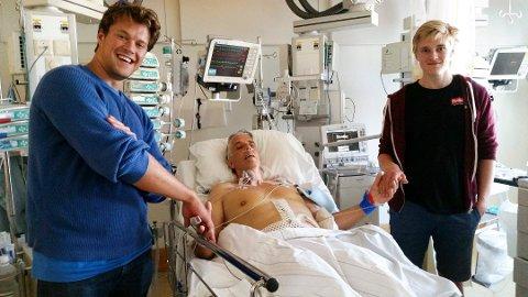 TRANSPLANTASJON: Levertransplantasjonen ble vellykket og en sliten, men lykkelig Jarle Bentzen i sykesengen lykkeønskes av sine sønner Joachim (t.v.) og Jørgen. Det er denne operasjonen som gjør Jarle ekstra sårbar. Foto: Privat