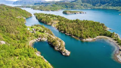 PRIVAT IDYLL: Småbruket og halvøya på venstre side i bildet ligg heilt ned til det tronge sundet som skil store Randøy og vesle Kvaløy.