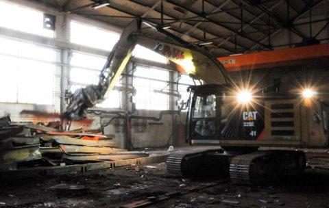 RIVINGEN HAR STARTET: Foreløpig er det kun en stor maskin som holder på med rivingsarbeidet på Smietangen. Etter hvert vil det nok komme både flere maskiner og flere arbeidere inn på tomta. – Framdriftsplanen tilsier at vi skal være ferdig i løpet av året, vi satser på å være ferdige til jul, sier Øystein Wingereid.
