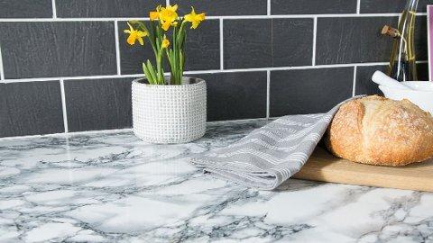 Her er det brukt selvklebende designfolie med marmorlook på kjøkkenbenken. Foto: Fantasi Interiør/ANB