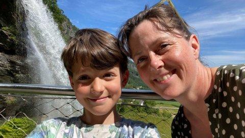 ENKLE GREP: Ferien blir ikke mindre koselig ved å være mer økonomisk. Her er Marie og sønnen Mats (9) foran Steinsdalsfossen i Hardanger. Foto: Privat